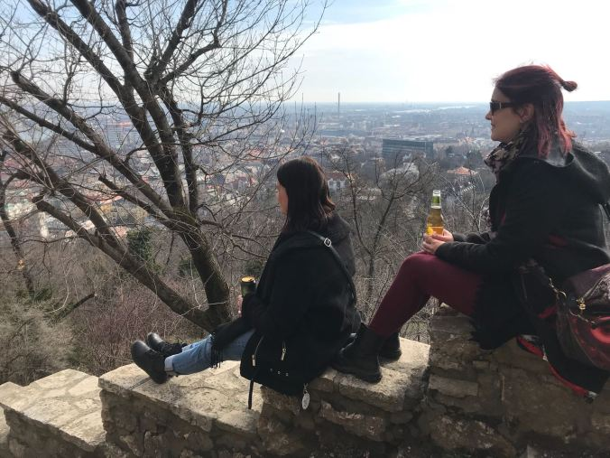 two girls are sitting on the stairs in front of the city view of budapest