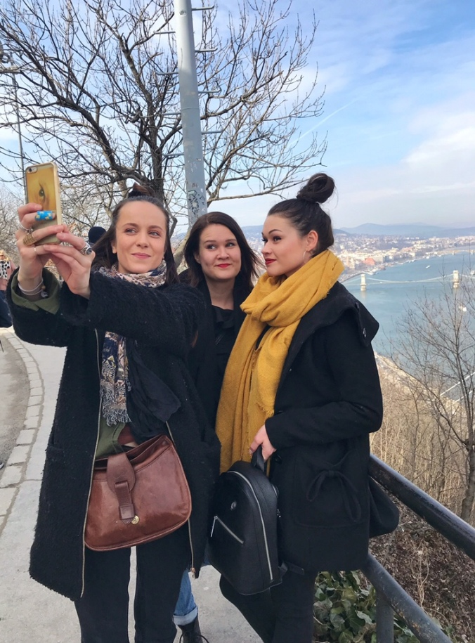 three girls are taking group selfie