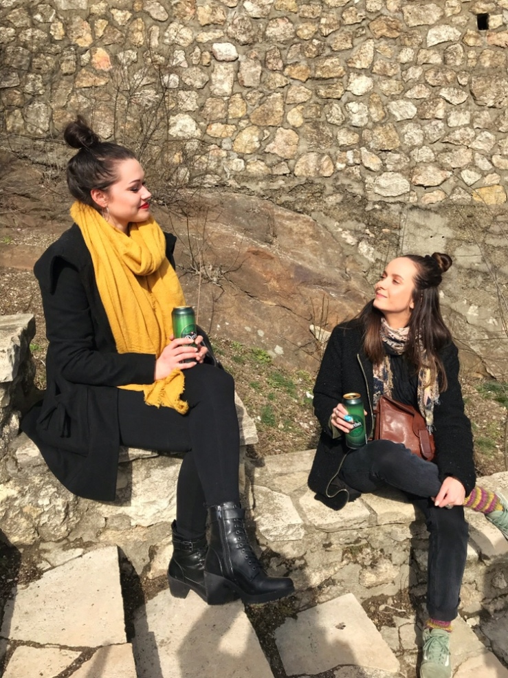 two girls are drinking beer and sitting on the stairs